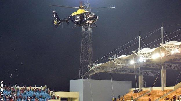 A police helicopter hovers over the stadium