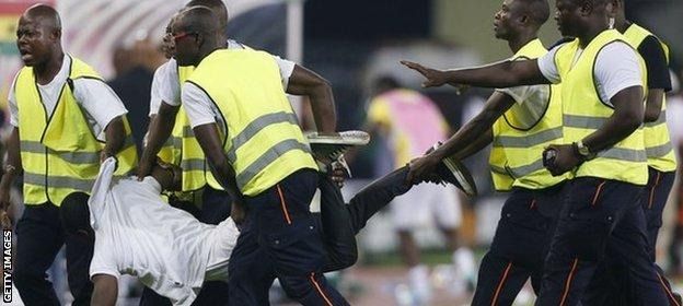 A spectator is carried off the pitch after trying to attack the referee