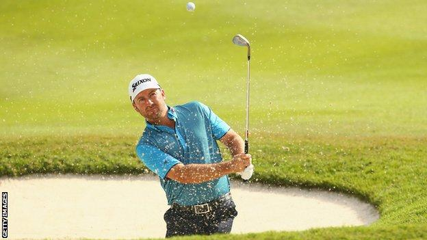 Graeme McDowell plays out of a bunker during the third round in Kuala Lumpur