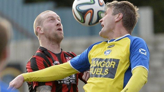 Crusaders midfielder Stephen O'Flynn contests a high ball with Bangor defender Colin Nixon