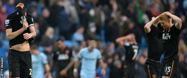 Hull players show their disappointment after conceding a laet goal at Manchester City