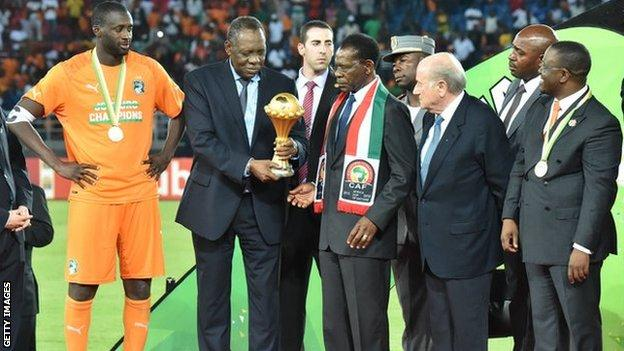 Yaya Toure wait to be handed the trophy, with Caf president Issa Hayatou to his right