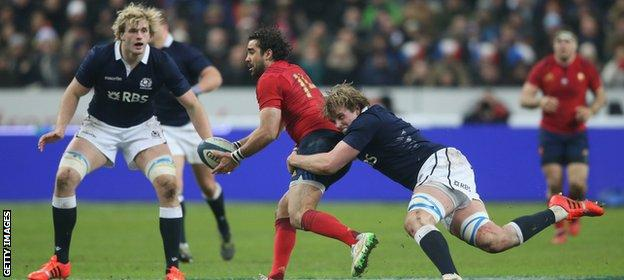 Yoann Huget of France is tackled by Jonny Gray of Scotland as brother Richie looks on during the Six Nations match at Stade de France