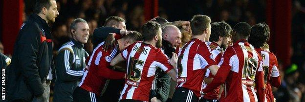 Brentford's players celebrate with Mark Warburton