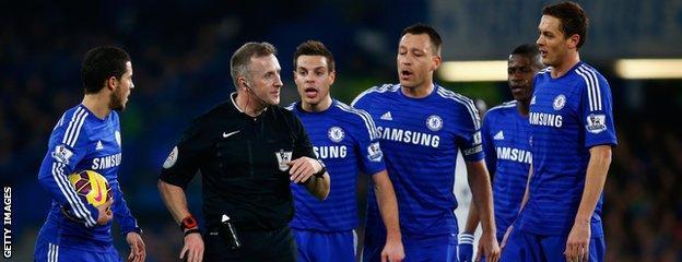 Chelsea's players surround referee Jon Moss