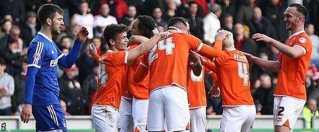 Blackpool players celebrate their opening goal against Forest