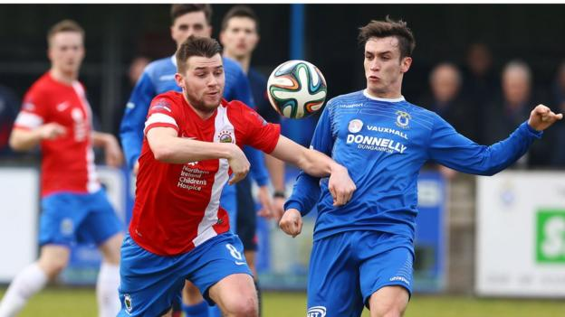 Linfield's Stephen Lowry contends for the ball with Swifts player Grant Hutchinson at Stangmore Park