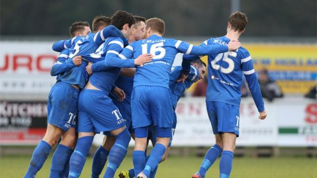 Ballinamallard players converge on Jason McCartney after he scores the penalty which ensured a last-gasp victory over Coleraine