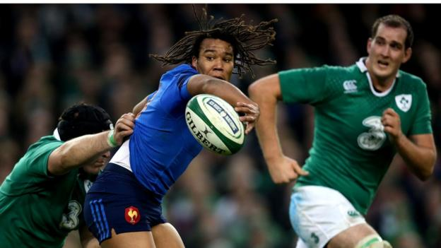 Teddy Thomas offloads the ball for France despite the attention of prop Mike Ross and second row Devin Toner