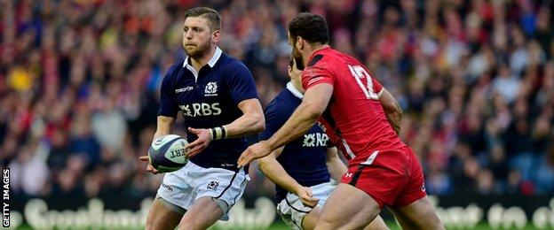 Jamie Roberts moves in to challenge Scotland's Finn Russell