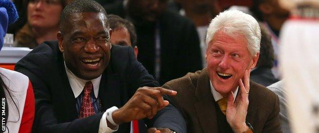 NBA legend Dikembe Mutombo talks with former president Bill Clinton