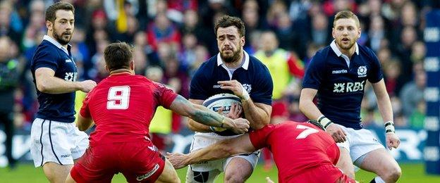 Alex Dunbar tries to break past Wales duo Rhys Webb and Sam Warburton