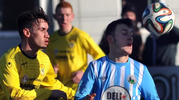 Warrenpoint Town's Johnny Frazer beats Dungannon Swifts midfielder Grant Hutchinson to the ball at Milltown
