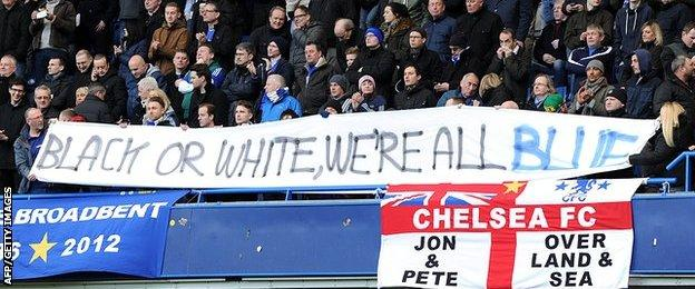"""Fans holding a banner reading: """"Black or white, we're all blue."""""""