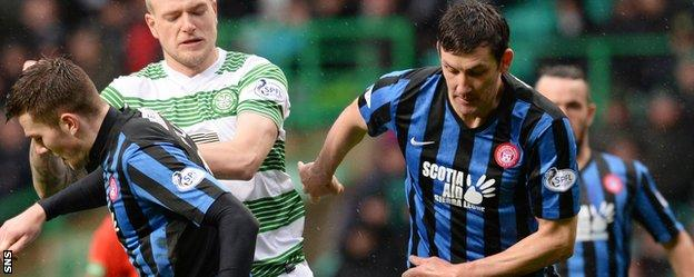 Martin Canning (right) challenges Celtic striker John Guidetti