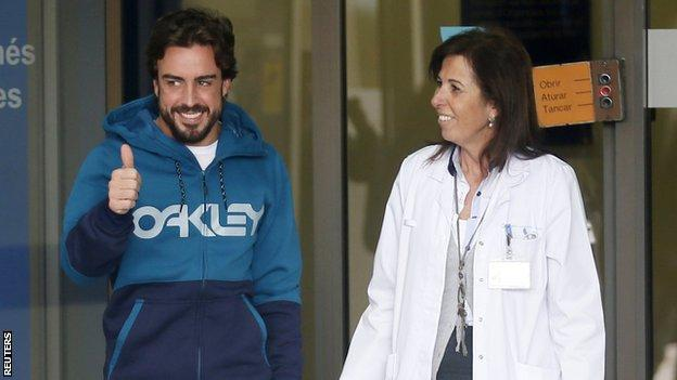 """McLaren""""s Formula One driver Alonso gestures to the media as he leaves a hospital where he has been hospitalized since Sunday, in Sant Cugat"""