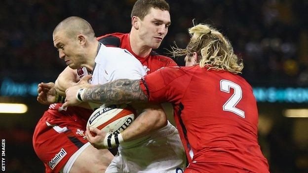England full-back Mike Brown is tackled by Wales' George North and Richard Hibbard (right)