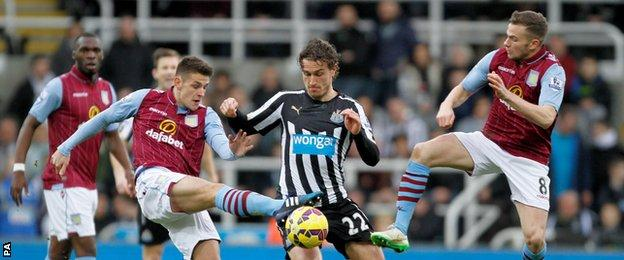 Aston Villa's Ashley Westwood (left) and Aston Villa's Tom Cleverley challenge Newcastle United's Daryl Janmaat