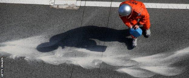 A track marshal covers the oil left by Kevin Magnussen's McLaren