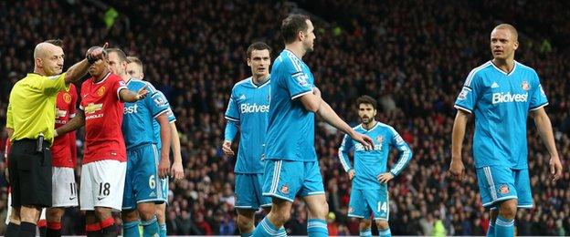 A bemused Sunderland defender Wes Brown (right) goes off after being red-carded at Manchester United