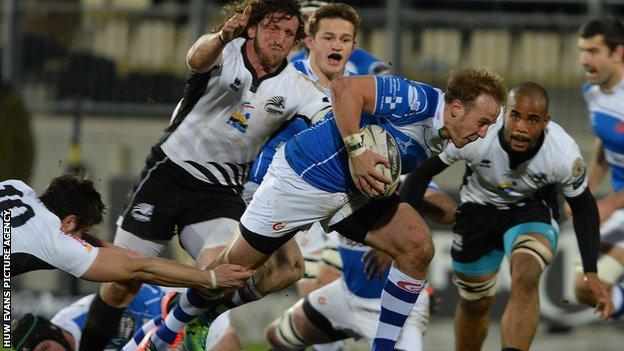 Ashley Smith on the attack for Newport Gwent Dragons is tackled by Zebre's Edoardo Padovani