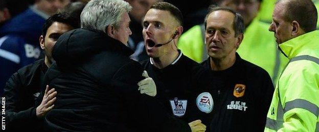 The assistant referee tries to calm Bruce down