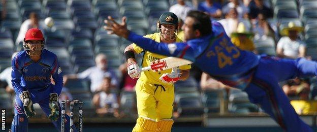 Afghanistan bowler Samiullah Shinwari dives for the ball off Australian batsman David Warner