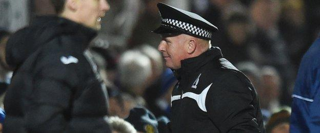 Peter Houston tries on a policeman's hat for size after the wind blew it onto the pitch.