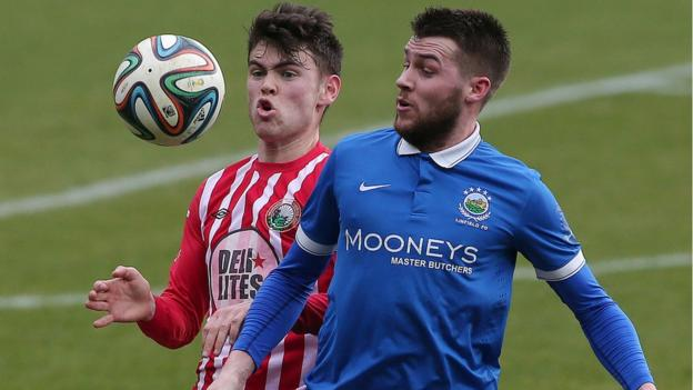 Conor McDonald of Warrenpoint Town competes for the ball against Linfield opponent Stephen Lowry