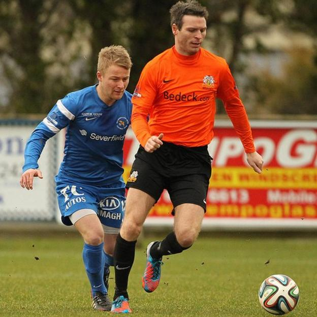 Ballinamallard United's John Currie closes in on Kevin Braniff of Glenavon