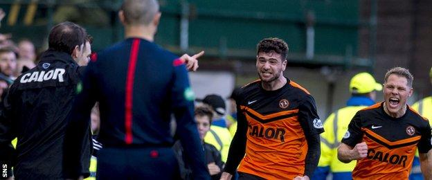 United striker Nadir Ciftci runs towards manager Jackie McNamara after scoring a penalty