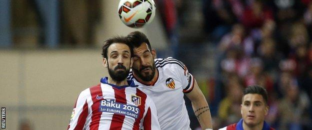Valencia's Alvaro Negredo challenges Juanfran of Atletico Madrid