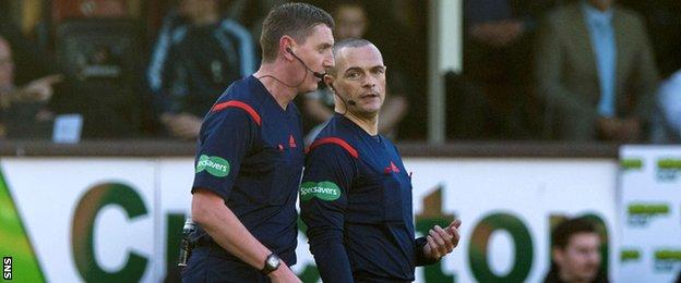 Referee Craig Thomson and assistant Graham Chambers discuss an incident