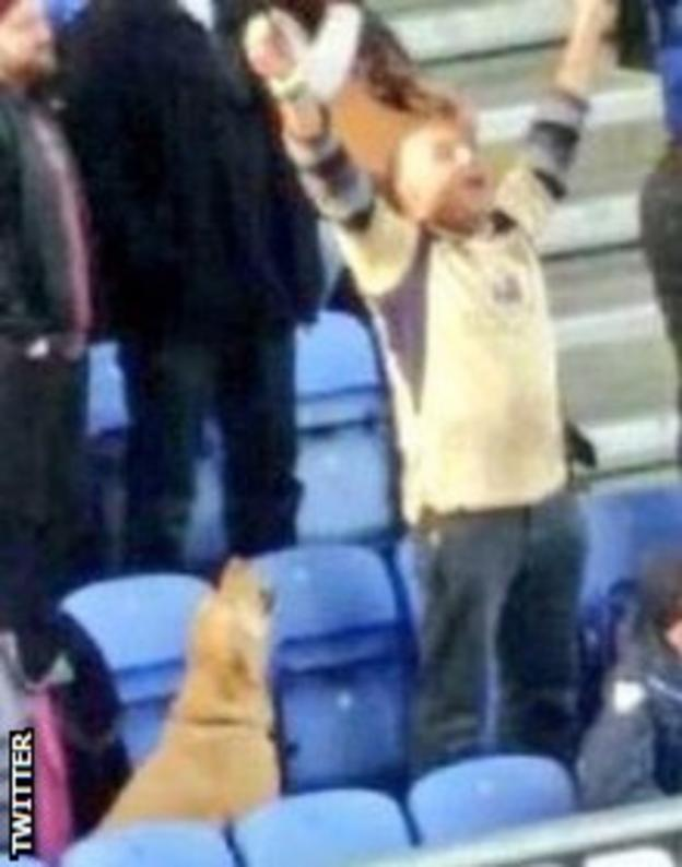 A Leeds fan celebrates his side's win over Wigan with his dog