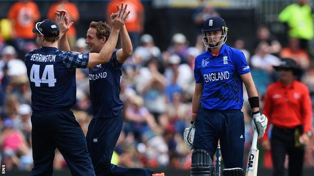 Richie Berrington and Josh Davey celebrate taking the wicket of England's Joe Root