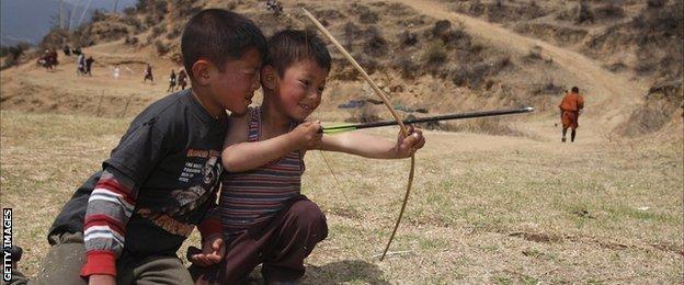 Small boys play with bow and arrow