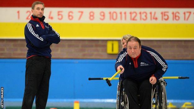 Tom Killin keeps his eye on his shot as coach Tony Zummack watches on