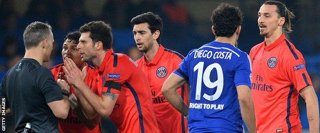 Paris St-Germain players surround referee Bjorn Kuipers
