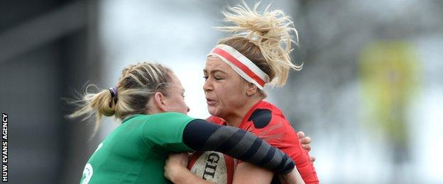 Wales centre Adi Taviner is tackled by Ireland captain Niamh Briggs at St Helen's