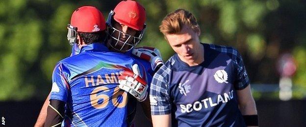 "Afghanistan batsmen Hamid Hassan (L) and Shapoor Zadran (C) celebrate as Scotland""s Richie Berrington (R) reacts"