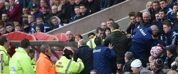 Police and stewards surround the Sunderland dug-out during the defeat by Aston Villa