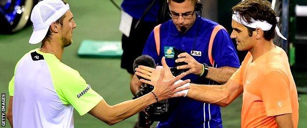 Andreas Seppi of Italy congratulates Roger Federer of Switzerland