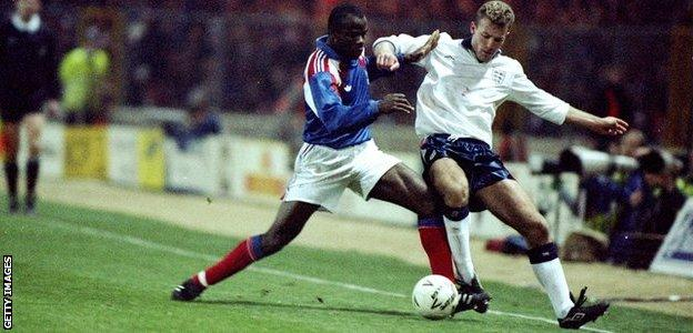 Alan Shearer is challenged by France's Basile Boli on his England debut