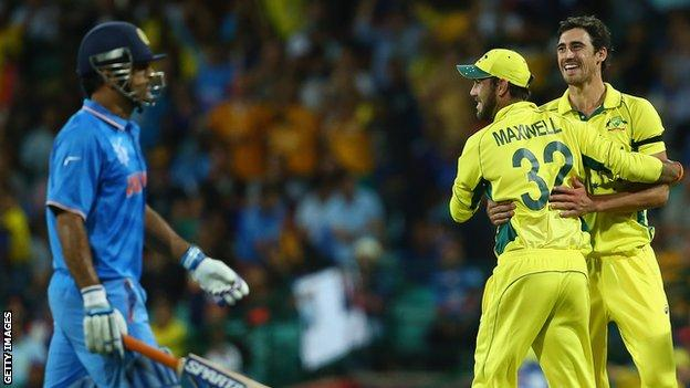 MS Dhoni of India looks dejected as Glenn Maxwell and Mitchell Starc of Australia celebrate his run out