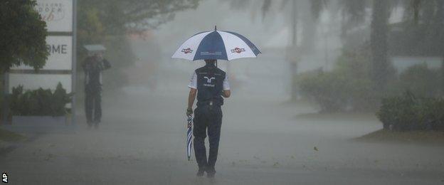 Williams crew member walks in the paddock with an umbrella