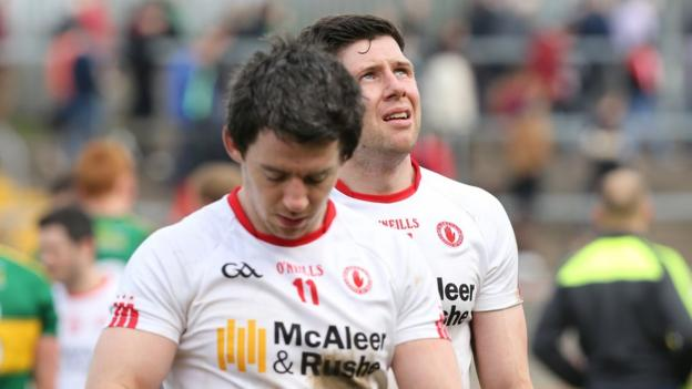 Dejected Tyrone duo Mattie Donnelly and Sean Cavanagh leave the Healy Park pitch after being held to a draw by Kerry which meant relegation to Division Two