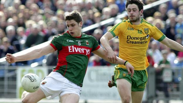 Mayo's Lee Keegan gets a shot in despite the efforts of Donegal opponent Ryan McHugh