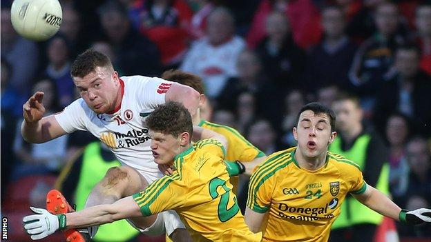 Tyrone's Ruairi McGlone is tackled by Michael Miller and Conor Morrison
