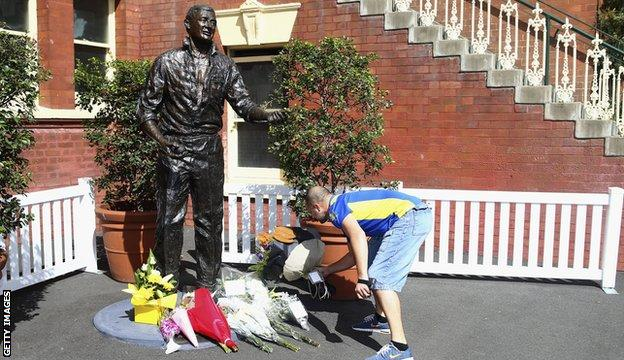 Richie Benaud tributes - a man lays flowers by a statue of Benaud