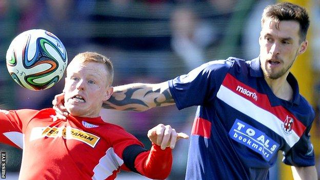 Cliftonville's George McMullan in action against Declan Caddell of Crusaders